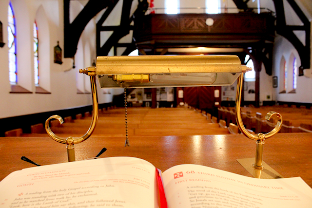 An open lectioanry on a wooden pulpit facing an empty church