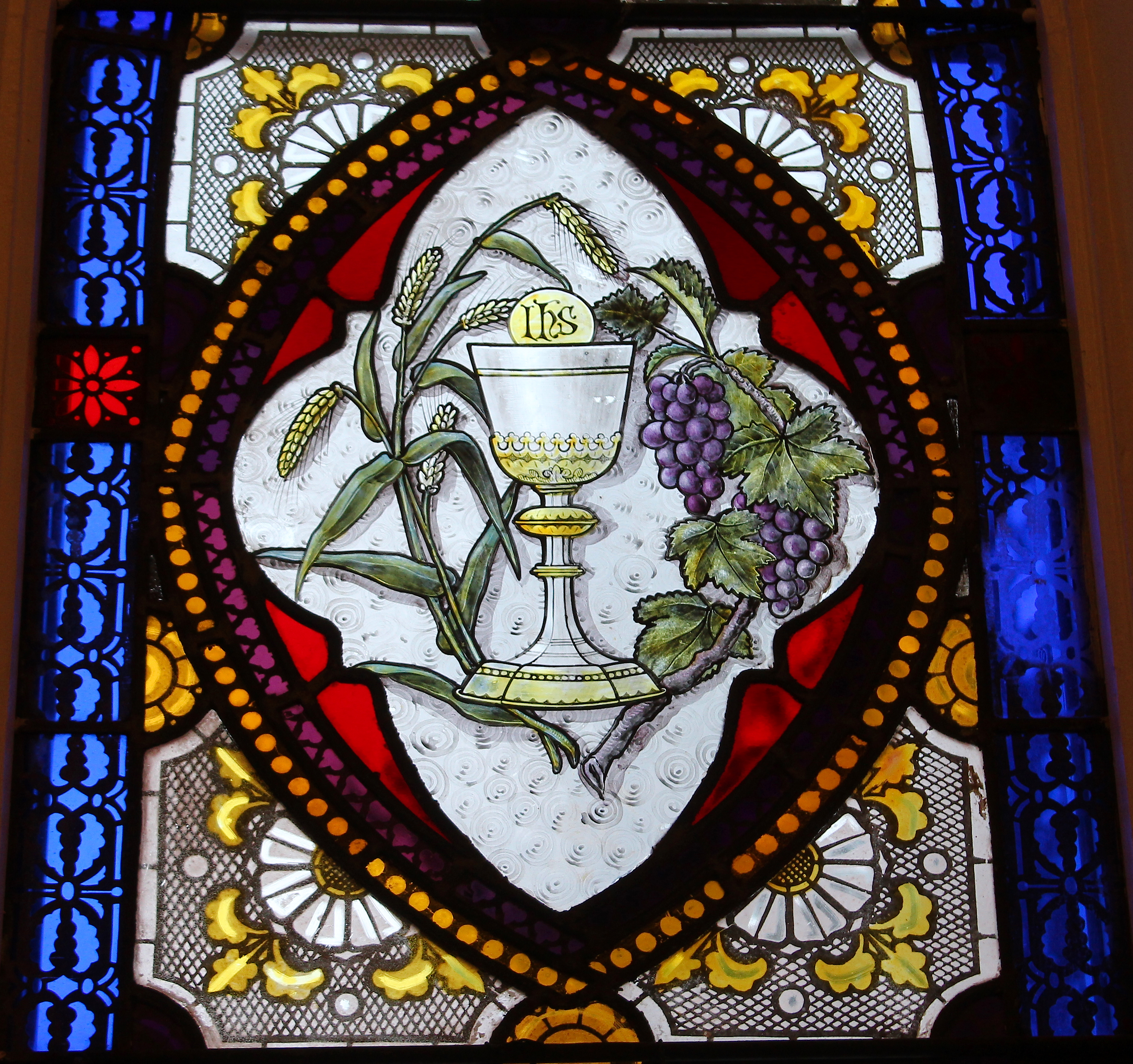 a stained glass window of a chalice and host, with wheat on one side and purple grapes on the other